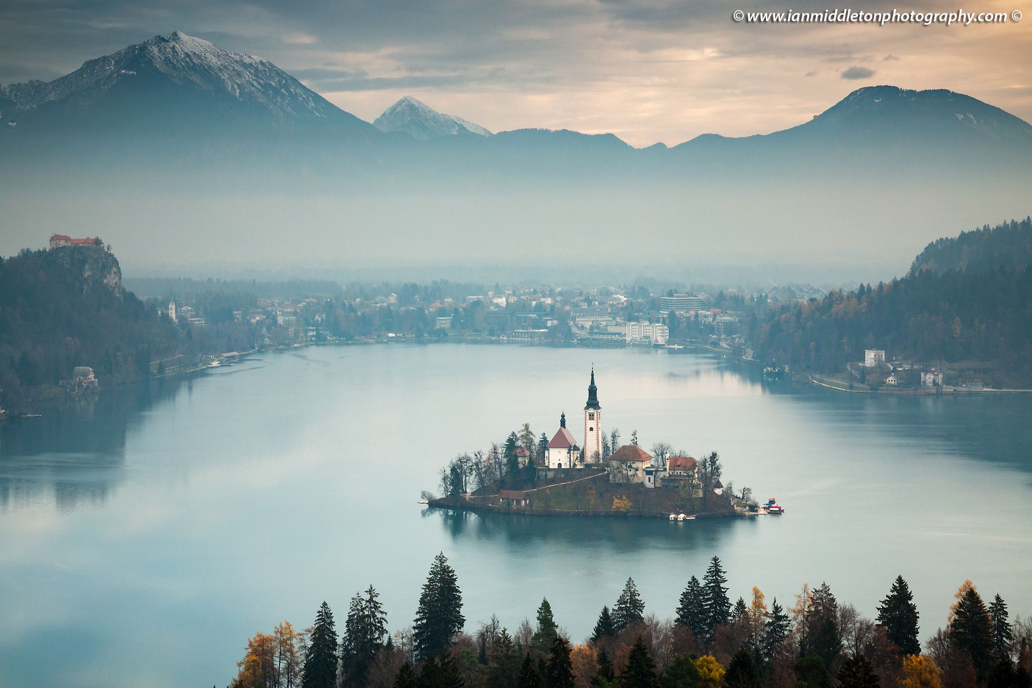 Morning view across Lake Bled to the island church and clifftop castle from Ojstrica, Slovenia.