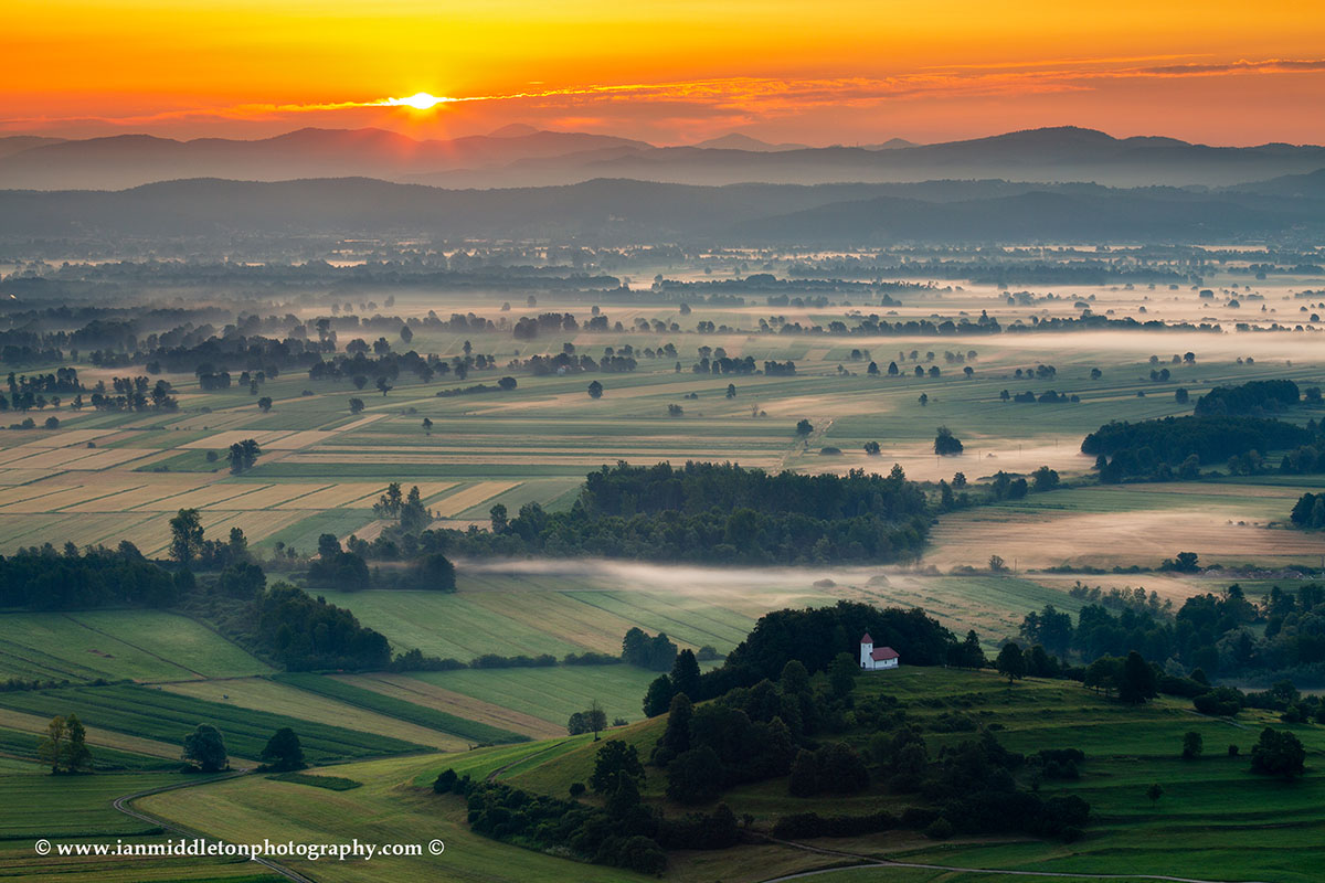 Sunrise over the Ljubljana Marshes and the church of Saint Lawrence.
